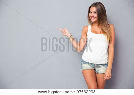Cute young woman pointing finger away over gray background. Looking at camera