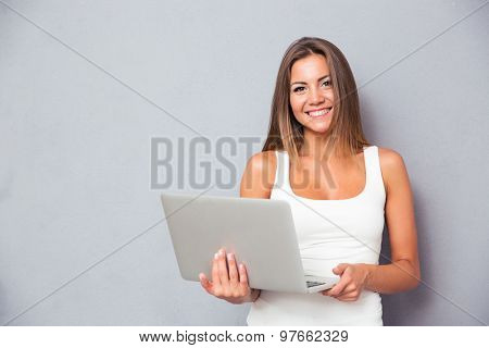 Smiling young woman standing with laptop over gray background