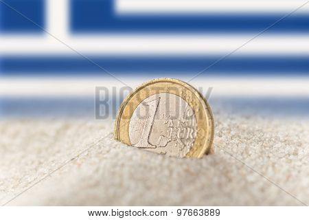 Euro coin in the sand with greek flag.