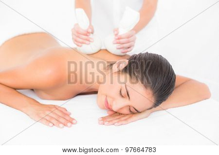 Beautiful brunette enjoying a herbal compress massage at the health spa