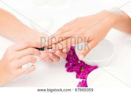 Close up of beautician applying nail varnish to female client nails at spa beauty salon