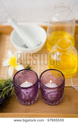 Close up view of a massage tray with candles and oil