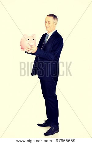 Full length side view businessman with piggybank.