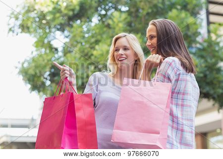 Happy women with shopping bags and pointing away outside
