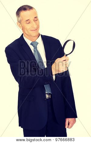 Businessman looking through a magnifying glass.