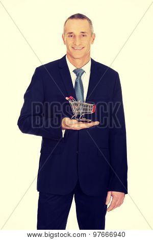 Mature businessman holding small shopping cart.