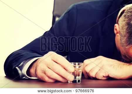Overworked mature man drinking vodka in office.