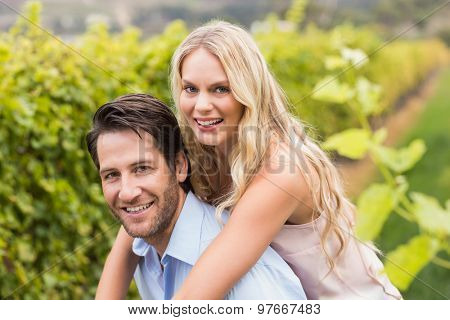 Young happy woman embracing young handsome man in the grape fields