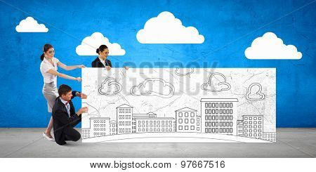 Team of businesspeople presenting banner with construction sketches