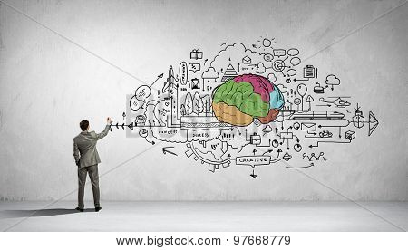 Back view of businessman drawing human brain on wall