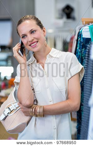 Smiling woman phoning next to clothes rail in clothing store