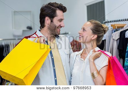Smiling couple with shopping bags looking at each other in clothing store