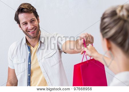 Smiling cashier giving shopping bag to woman in clothing store