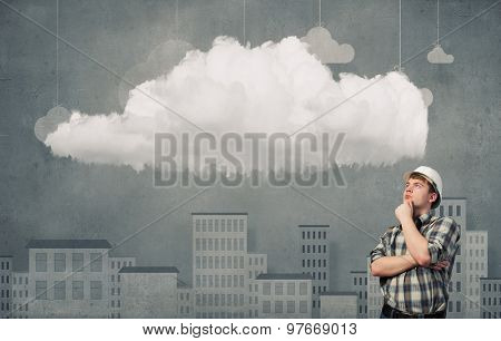 Young man builder looking thoughtfully at cloud in sky. Idea concept