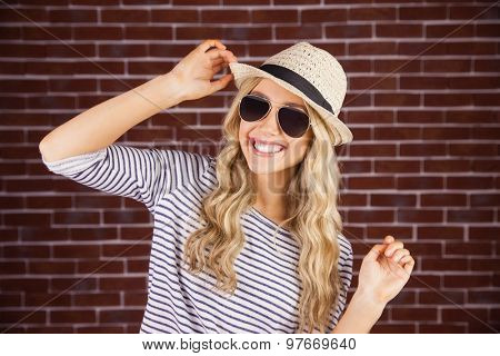 Portrait of gorgeous smiling blonde hipster posing with straw hat against red brick background