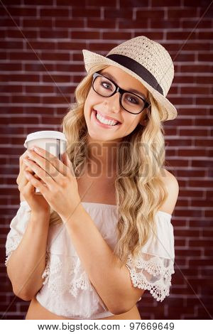 Portrait of gorgeous smiling blonde hipster with take-away cup against red brick background