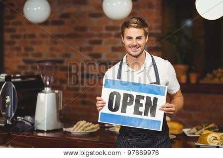 Portrait of a handsome waiter presenting open sign at the coffee shop
