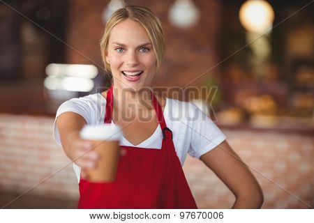 Portrait of a waitress handing a mug of coffee at the coffee shop