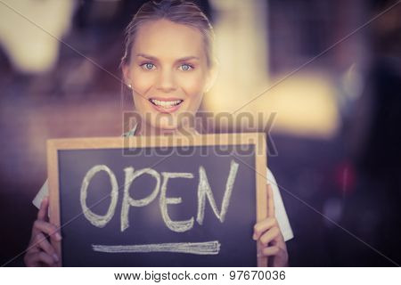 Portrait of smiling blonde waitress showing chalkboard with open sign at coffee shop