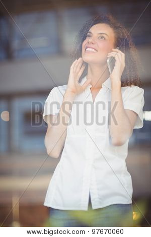 Smiling woman talking on the phone at the coffee shop