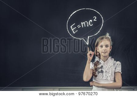 School girl pointing at science formula with finger