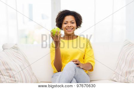 people, food, healthy eating and dental care concept - happy african american young woman with green apple sitting on sofa at home