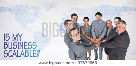 Smiling business team standing in circle hands together against background with world map