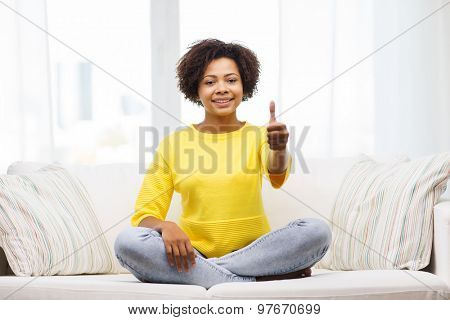 people, ethnicity, gesture and leisure concept - happy african american young woman showing thumbs up and sitting on sofa at home
