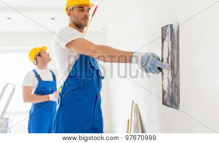 building, repair, teamwork and people concept - two builders in hardhats and overalls with spatula and painting roller repairing room