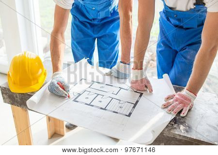 building, renovation, repair, teamwork and people concept - close up of builders discussing blueprint indoors