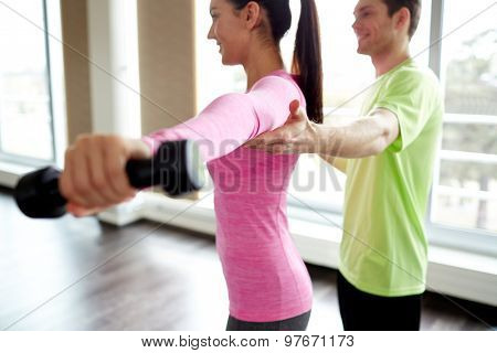 fitness, sport, exercising and people concept - smiling young woman and personal trainer with dumbbells flexing muscles in gym
