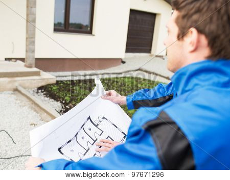building, construction and people concept - close up of builder with blueprint front of house outdoors