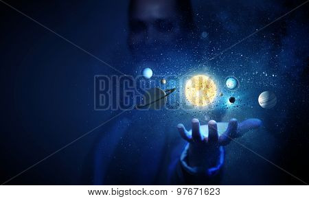 Young businesswoman holding in palm planet of sun system