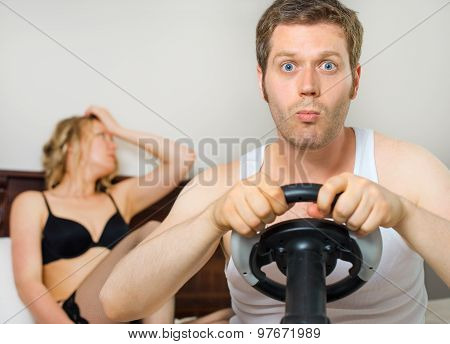 Video Game Addiction. Man Playing Video Game With Steering Wheel, Upset Woman On Background.
