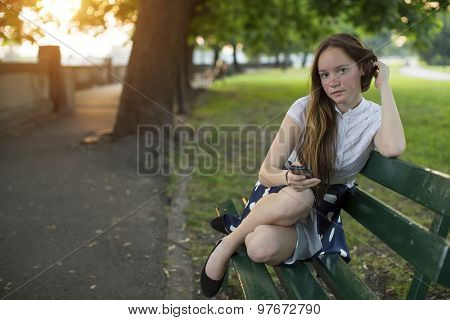 Young girl sits with a smartphone on a bench in a city Park.