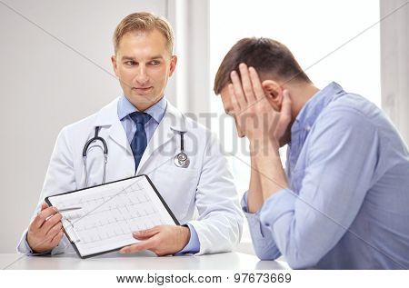 medicine, health care, people and cardiology concept - male doctor and patient with cardiogram on clipboard