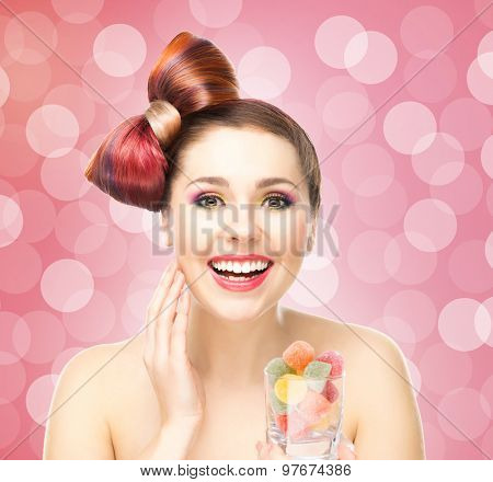 Beautiful smiling woman holding a glass with candies.