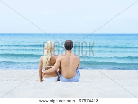 Loving couple sitting and embracing on a tropical summer beach
