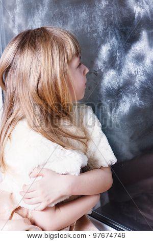 little girl looking upwards through frosty window