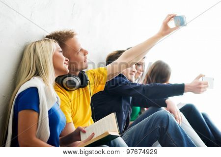 Group of happy students being on a break taking selfie. Focus on a happy girl and boy in headphones. Background is blurry