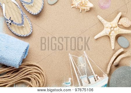 Travel and vacation items on sea sand. Top view with copy space