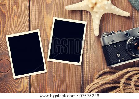 Travel and vacation photo frames and items on wooden table. Top view. Toned