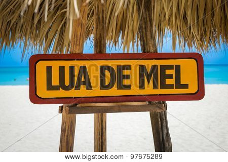 Honeymoon (in Portuguese) sign with beach background