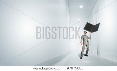 Angry young businessman in rage throwing laptop