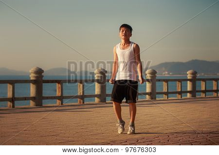 Vietnamese Boy Rests Hands Down On Embankment At Dawn