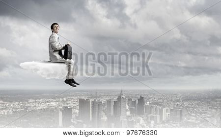 Businessman in suit sitting on cloud in isolation