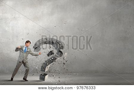 Young furious businesman crashing stone question mark