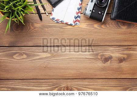 Camera and supplies on office wooden desk table. Top view with copy space