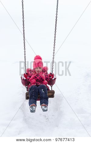 little girl playing in a snow pile.