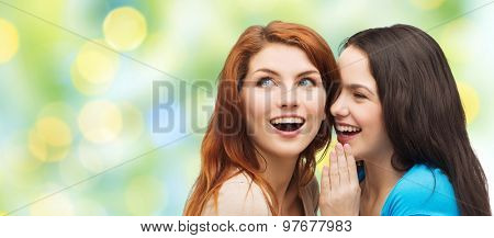 friendship, secrecy and people concept - two smiling girls or young women whispering gossip over green lights background
